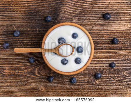 White yogurt in natural wooden bowl with blueberries. Top view on rustic background.