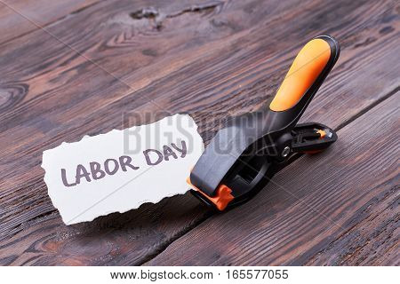 Labour Day card and clamp. Plastic clamp on wooden background. Build the atmosphere of holiday.