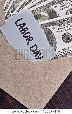 Labour Day card near dollars. Envelope with money and card. Reward for hard work.