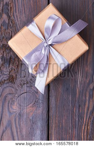 Top view of present box. Wisteria color ribbon bow. Celebration begins with gifts.