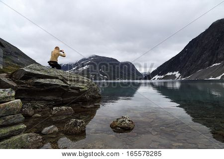 LAKE DYUPVATNET, NORWAY - JULY 6, 2016: An unknown young woman takes a picture Norwegian mountain landscape near the lake.