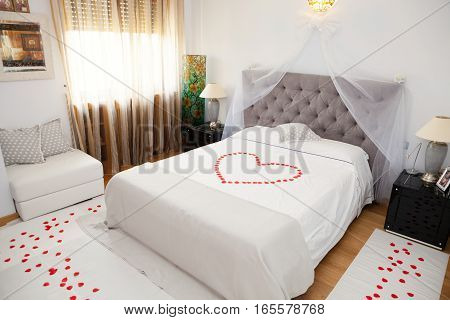 Bridal Bedroom. Interior room, marriage bed. Rose petals on the bed that form a heart and on the floor. Bedside tables, sofa and window curtain.