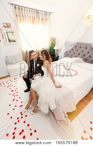 Newlyweds in bedroom with heart. Love, tenderness. Just married. First night. On the bed rose petals heart-shaped.