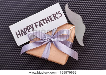 Card and mustache on gift. Present box on black surface. Stylish congratulation for dad.