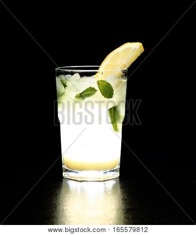 Glass Of Lemonade With The Slice Of Lemon And Mint Reflected On The Smooth Surface. Dark Background