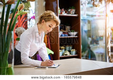 Confident woman is working in flower shop. She is standing near table and writing in notebook with concentration