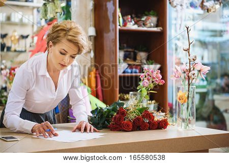 Serious female florist is working with documents in her store. She is standing near bouquet of roses