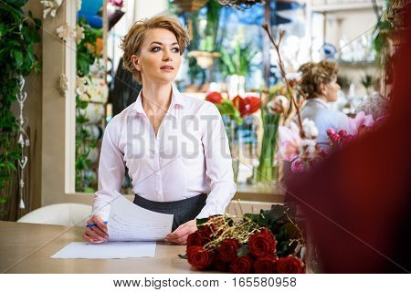 Pensive woman is waiting for customer in flower shop. She is standing at counter and holding documents