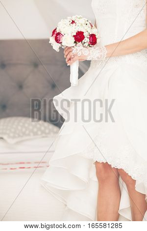Marry, marriage bouquet and wedding dress. Bride at home. Bridal bed. Figure of a woman with a bouquet of flowers in her hands in front of the bridal bed in the bedroom. Sensuality and feminine delicacy. White wedding dress.