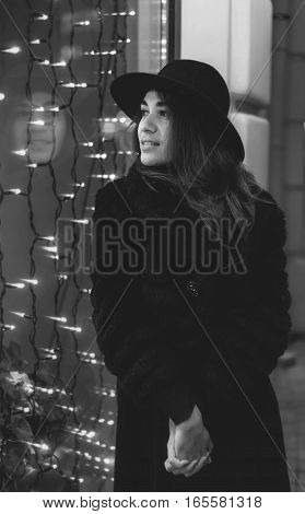 Outdoor fashion portrait of stylish young woman. Urban city street style. Black and white art photography monochrome
