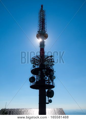 TV transmitte tower silhouette with sun hidden behind and blue sky background.