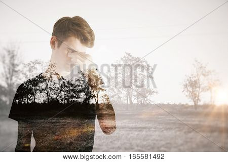Pensive young man on dull landscape background. Apathy concept
