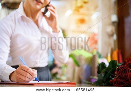 Confident woman is communicating with client on smartphone. She is writing and smiling. Focus on her hand