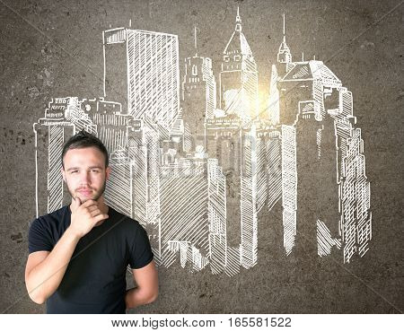 Businessman thinking and drawing city panorama on wall