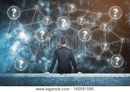 Confused man sitting on rooftop with question marks. Confusion concept