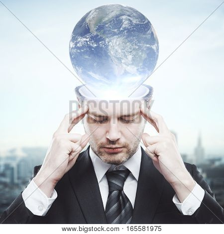 Pensive young businessman with abstract globe brain. Global thinking concept.