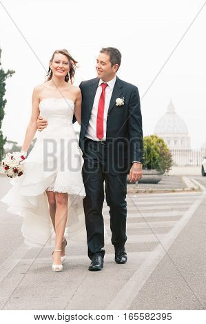 Newlyweds bride and groom walking along the street. Rome, Italy. Smiling couple walking side by side on an asphalt road. In the distance, with plenty of light, the Basilica of St. Peter at the Vatican.