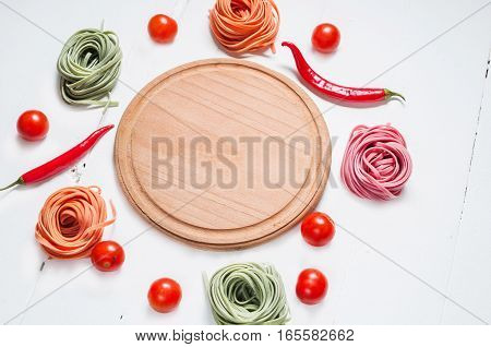 Colorful rolled pasta cherry tomatoes on the white wooden background.