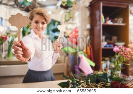 Buy this wonderful thing. Confident female florist is posing and smiling. Focus on wooden figure in her hand