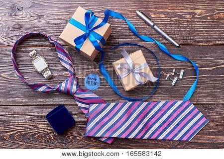 Father's Day card near presents. Striped tie near watch. When father is a businessman.