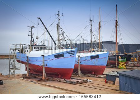 Sail Boat With Workers In A Boatyard Being Repaired