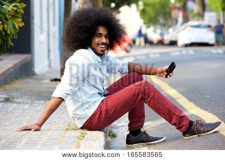 Happy Man With Mobile Phone Sitting On Sidewalk