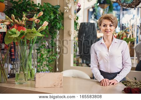 Welcome to my flower shop. Friendly woman is standing near bouquets and smiling. She is looking at camera with joy