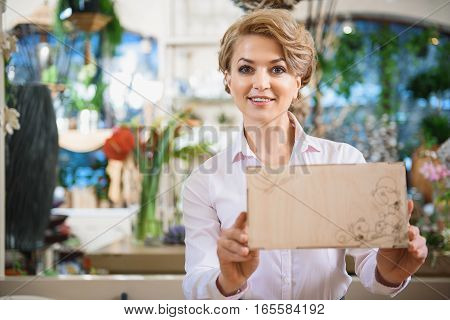 Confident female florist is showing wooden box with flower weave. She is standing with friendly smile