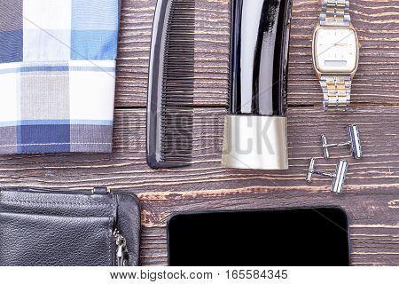 Tablet, cologne and watch. Plaid shirt and accessories. Impact of fashion on society.