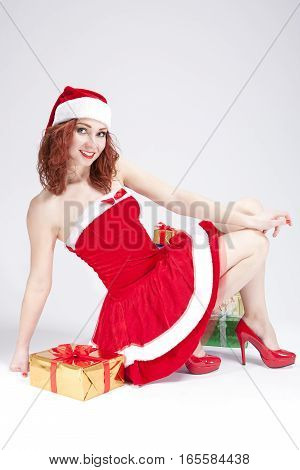 Christmas and New Year Concept and Ideas. Positive Caucasian Santa Helper Girl Posimng with Gifts Against White. Vertical Image