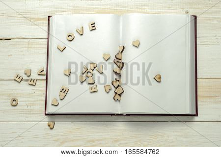 The word love a lot of hearts on a background of book on a wooden table. Back to school copy space. Education background.