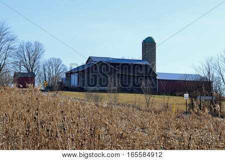 A barn with weathered barn boards, silo and lightning rods on the roof.