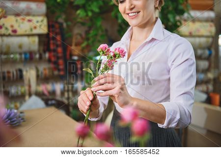 Happy female florist is holding pink roses and looking at it with admiration. She is smiling