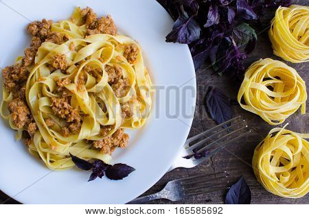 Tagliatelle with bolognese sauce on wooden background. Traditional Italian pasta Bolognaise with a spicy tomato based meat sauce garnished with fresh basil. Top view.