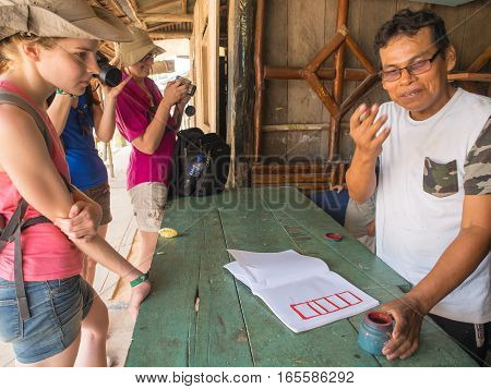 Santo Tomas Peru - May 17 2016: Peruvian man showing the calligraphy to the tourists