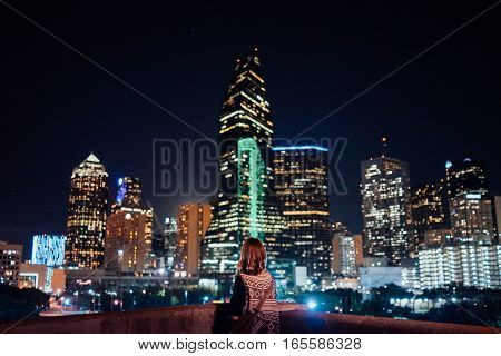The Traveling Teenager Girl Looking at Dallas Skyline at Night