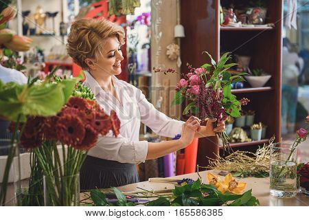 These flowers are perfect. Happy female florist is satisfied with her work. She is standing and smiling