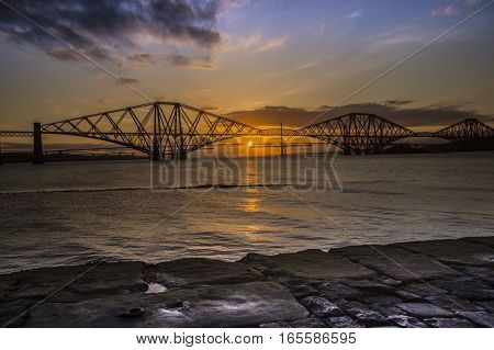 standing on the jetty watching the sun go down behind the Forth Rail Bridge