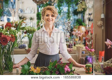 My small business is booming. Successful female florist is standing at counter near bouquets and laughing. She is looking at camera with happiness