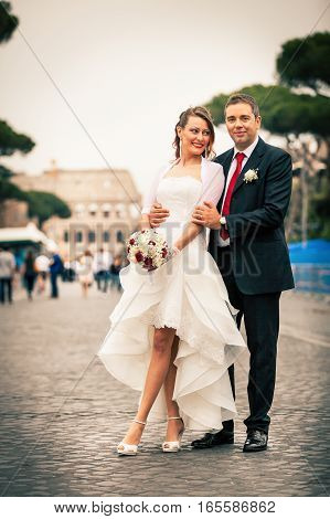 Newlyweds in the city. Happy married couple. A smiling groom embracing his bride in white wedding dress. They are located in the historic center of Rome, Italy. The women dressed in white holding a bouquet of flowers.