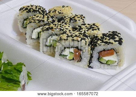 Philadelphia sushi roll with with Salmon, Cream Cheese, Salad Leaf and Avocado inside. Sesame outside
