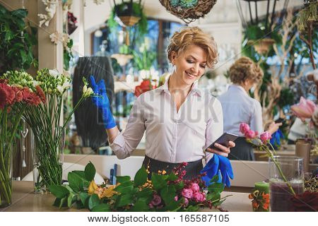 Joyful woman is using smartphone while working in flower shop. She is standing in rubber gloves and smiling