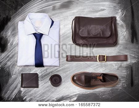 Men's Clothing on a blackboard with chalk. Shirt, tie, belt, purse and shoes