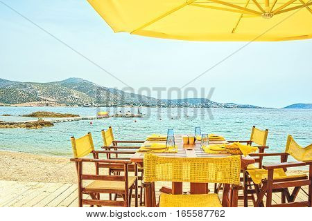 Picturesque landscape with a beach café on the seafront in Greece in a sunny summer morning