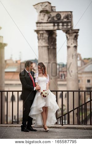 Newlyweds in the ancient city. Happy married couple. Rome, Italy. The women dressed in white holding a bouquet of flowers. Behind them an imposing Roman column, ancient ruins. Imperial Forums, Rome. Italy.