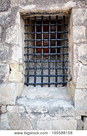Barred window in the stone wall of the castle Santa Barbara, Alicante