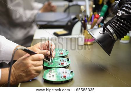Electronics Manufacturing Services Manual Assembly Of Circuit Board Soldering close-up of the hand women hold tool.