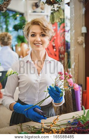 Excited female florist is making bouquet and smiling. She is holding bunch of little roses and looking at camera with joy