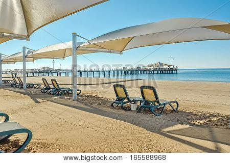 Sandy beach with sun loungers and parasols on the seafront in sunny summer day. Foreground blurred