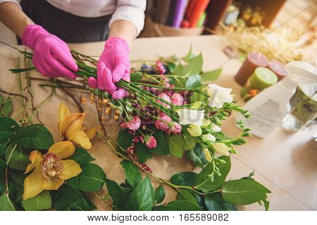 Top view close up of female hands making bouquet carefully. Woman is standing at table in workshop